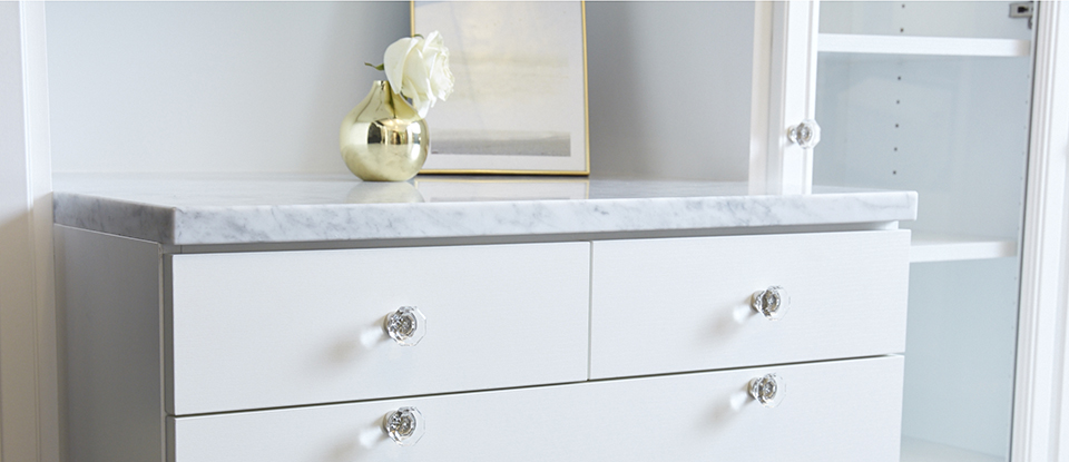 Close Up Image of White Dresser with Granite Counter Top