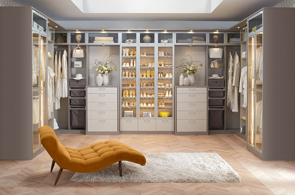 Gold gray and white walk in closet with a lounging chair