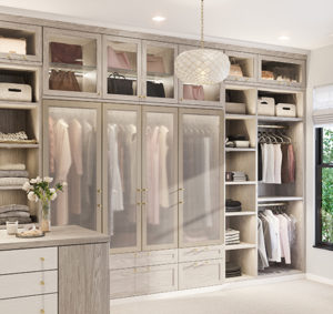 Light tan walk-in closet with blush accessories displayed
